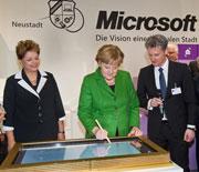"""Bundeskanzlerin Angela Merkel trägt sich in das Goldene Buch der digitalen Stadt """"Neustadt"""" von Microsoft ein."""
