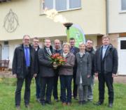 Bürgermeister Junghans (l.) und Jörg Hartmann, Geschäftsführer EnergieNetz Mitte (3. v. l.), überreichen der ersten Kundin am Gasnetz Blumen.