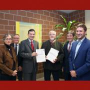 Der Erste Landesbeamte des Ortenaukreises überreicht die immissionschutzrechtliche Genehmigung zweier Windräder auf dem Nillkopf an Vertreter der Bürgerenergie.
