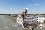 Heizungsbaumeister Lars Ost prüft auf dem Dach die gerade angelieferten Bauteile für die Solaranlage.