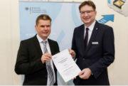 Thomas Gast, Fachbereichsleiter beim BSI (l.), überreicht Dr. Volker Kruschinski, Vorstandsvorsitzender der Schleupen AG, auf der E-world 2018 das Zertifizierungsschreiben zum Sub-CA.