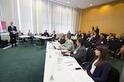 Jon Abele, Partner und Leiter Öffentliche Auftraggeber bei BearingPoint (links), vor der Jury und dem Plenum des 14. E-Government-Wettbewerbs.