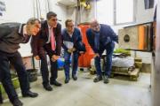 Vertreter der Stadtwerke Rüsselsheim und der Stadtwerke Dreieich werfen gemeinsam einen Blick in die Brennkammer der Rüsselsheimer Holzhackschnitzelanlage.