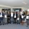 Unternehmensvertreter mit Zertifikaten nach erfolgreicher Teilnahme im Simulationszentrum.