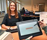 Ramona Berg, Mitarbeiterin im Bürgerbüro Ganderkesees, erklärt, wie man per Tablet unterschreibt.