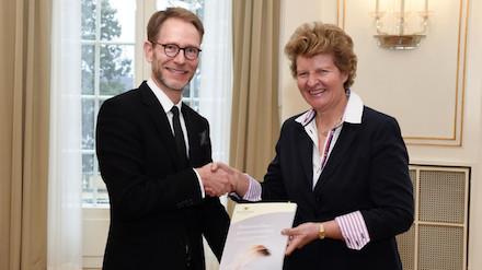 Staatssekretär Florian Stegmann erhält den ersten Bericht des Normenkontrollrats Baden-Württemberg von der Vorsitzenden des Gremiums, Gisela Meister-Scheufelen.