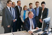 BfJ-Präsident Heinz-Josef Friehe unterzeichnet den ersten Vorgang in der E-Akte Bund (im Hintergrund Vertreter der am Pilotprojekt beteiligten Behörden und des Software-Herstellers Fabasoft).