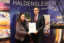 Staatssekretär Thomas Wünsch übergibt der zweiten stellvertretenden Bürgermeisterin, Carola Aust, den Förderbescheid für ein Digitalisierungszentrum in Haldensleben.