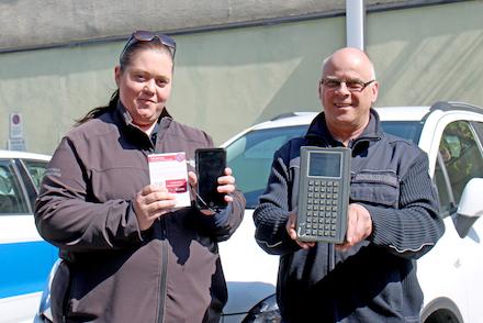 Zwei Überwachungskräfte der Stadt Detmold zeigen die alte und neue Technik: Bisher mussten die Verwarnungen über ein schweres Gerät inklusive Drucker ausgestellt werden (rechts), jetzt reichen Smartphone und Kartenblock (links).