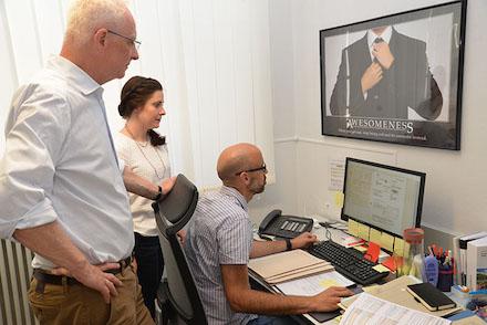 Patrick Schmitt (sitzend) erläutert OB Wolfram Leibe und Referentin Nina Womelsdorf das Programm zur elektronischen Erfassung von Rechnungen in Trier.