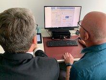 Ein Mitarbeiter der Verwaltung Nidderau zeigt Hessen-CIO Patrick Burghardt, wie ein Ausweis komplett digital beantragt werden kann.