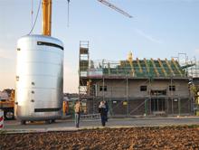"""Die im Bau befindliche Wärmezentrale für das Baugebiet """"Auf dem Zanger"""" in Kempen, kurz bevor der 50 Kubikmeter fassende Wärmespeicher durch das Dach ins Innere gehoben wurde."""