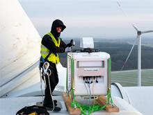 Ein ForWind-Wissenschaftler installiert das laseroptische Lidar-Messgerät zur Erfassung der Nachlaufströmung auf der Gondel einer Windenergieanlage der Firma eno energy.