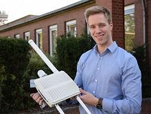 Felix Schwerter zeigt, wie ein einzelnes Gateway aussieht. Das Gerät ist etwa so groß wie ein DIN-A-4-Blatt und wird mit kleinen Antennen versehen.
