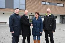 Die REWAG-Vorstände Bernhard Büllmann und Torsten Briegel, Bürgermeisterin Angelika Ritt-Frank und Bauamtsleiter Franz Wudi vor der Mintrachinger Sporthalle.