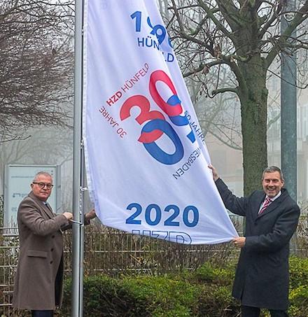 HZD-Direktor Joachim Kaiser (l.) und Technischer Direktor Thomas Kaspar hissen die Jubiläumsflagge vor der HZD-Zentrale.