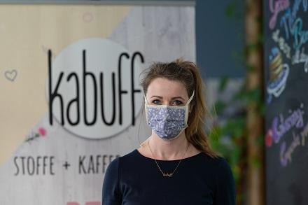 Vanessa König, eine der Inhaberinnen vom kabuff Stoffladen & Café und Mitiniatorin des Jenaer-Projektes, mit einem Modell der Mundmasken.