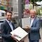 Oberbürgermeister David Langner (l.) und evm-Vorstandsvorsitzender Josef Rönz zeigen die Luftsensoren, die in Kürze an Laternenmasten entlang der Löhrstraße montiert werden, um die Luftqualität zu messen.