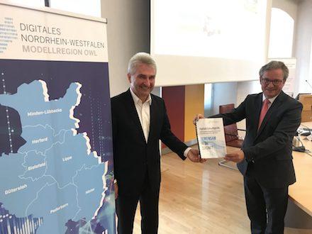 Paderborns Bürgermeister Michael Dreier (r.) übergibt eine Absichtserklärung an NRW-Wirtschaftsminister Andreas Pinkwart, welche die Zusammenarbeit in Ostwestfalen-Lippe nach Auslaufen der Landesförderung beschreibt.