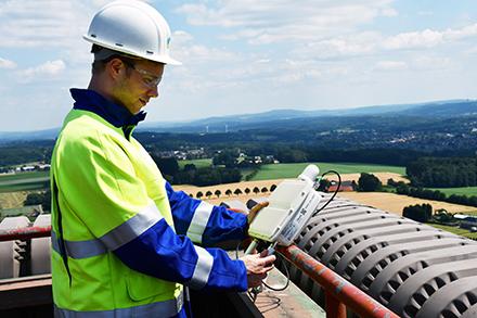 SWTE Netz-Mitarbeiter Felix Schwerter nimmt eines der Gateways für das neue LoRaWAN-Netz auf dem Dach des Kesselhauses des Kraftwerks Ibbenbüren in Augenschein.