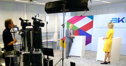 Digitales Kommunalforum: Der AKDB-Vorstandsvorsitzende Rudolf Schleyer mit Fernsehmoderatorin Julia Büchler.