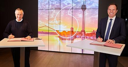 Vodafone-CEO Hannes Ametsreiter und Oberbürgermeister Stephan Keller unterzeichnen eine Vereinbarung für schnelleren Gigabit-Ausbau in Düsseldorf.