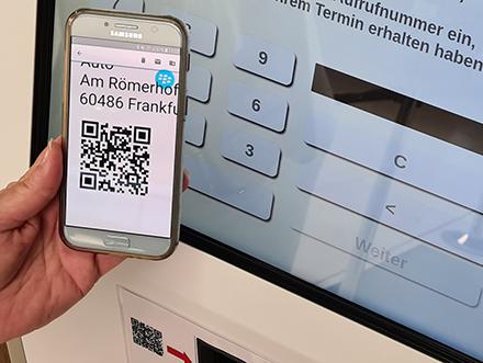 Bürger können sich mit Vorgangsnummer und QR-Code an den digitalen Terminals der Stadt Frankfurt am Main registrieren.