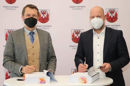 Oberbürgermeister Holger Kelch (l.) und DIKOM-Verbandsvorsteher Oliver Bölke besiegeln die Zusammenarbeit.