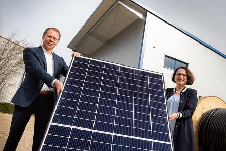 Der REWAG-Vorstandsvorsitzende Torsten Briegel und Oberbürgermeisterin Gertrud Maltz-Schwarzfischer mit einem Solar-Modul vor der neuen PV-Anlage.