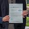Landrat Stefan Frey (l.) und IT-Leiter Thomas Eberhard (r.) nehmen die Zertifizierungs-Urkunde von Franz Obermayer von der complimant AG entgegen.
