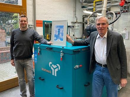 Claus-Heinrich Stahl (rechts) und Markus Henning vor dem mit dem für Blaue Energie zertifizierten BHKW.